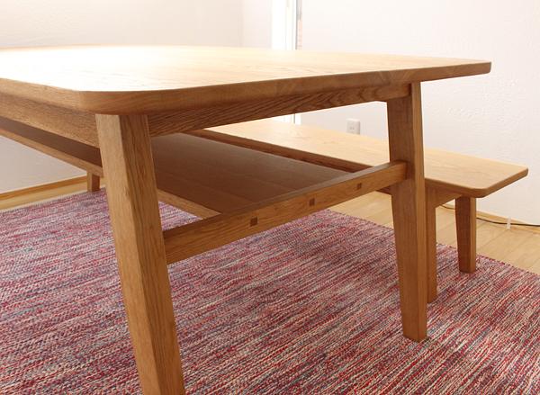ナラの木のダイニングテーブルとベンチ。天板の下にはモノを置けるスペースがあります。